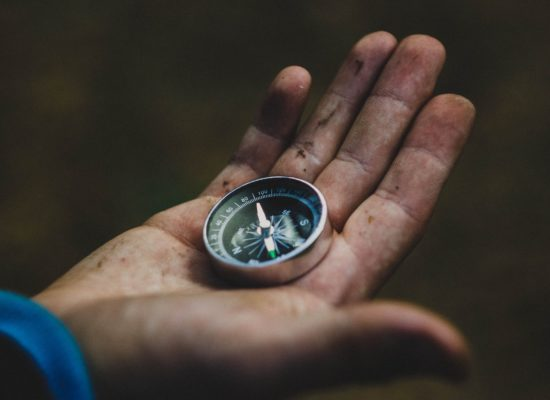 image of hand holding a compass